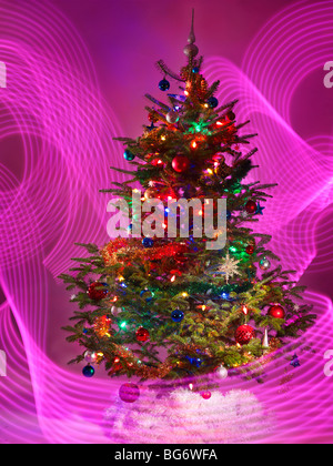 Decorated Christmas tree with purple lighting effects around it - Stock Photo