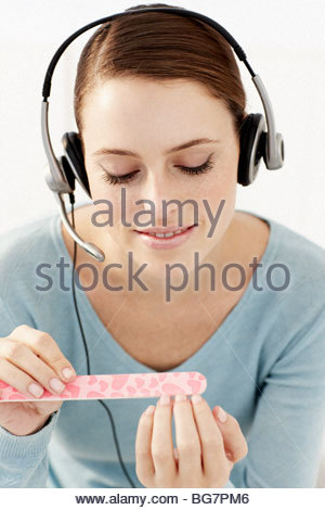 Woman wearing headset and filing fingernails - Stock Photo