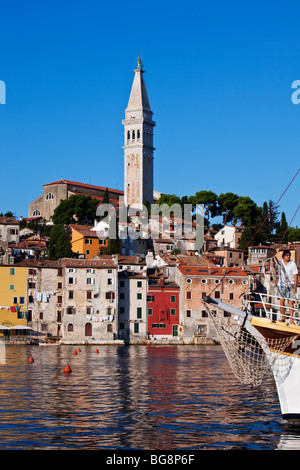 Boat entering Rovinj Old Town harbour Istria Croatia - Stock Photo