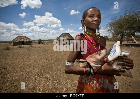 A Maasai woman in Tanzania, Africa holds food staples from an NGO. - Stock Photo