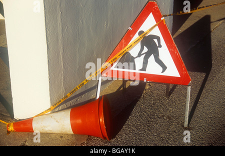Red and white Roadworker sign and traffic cone on its side with yellow tape stating Wet Paint beside cream painted - Stock Photo