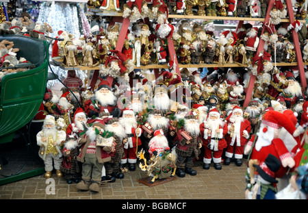 A large variety of Father Christmas models for sale in a store - Stock Photo