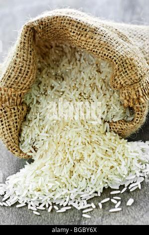 Raw long grain white rice grains in burlap bag - Stock Photo