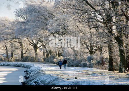 A winter scene with a couple strolling along the towpath of the frozen Caledonian Canal - Stock Photo