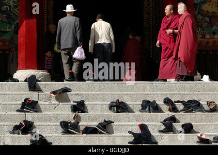 Tibetan monks in the robes of the Gelukpa order standing on the stairs in front of the assembly hall, where taken - Stock Photo