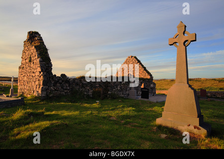 cemetery in Carna near Galway and Roundstone with Celtic cross and roofless church at sunset , Connemara, Ireland - Stock Photo