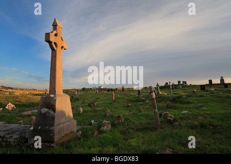 cemetery in Carna near Galway and Roundstone with Celtic cross at sunset, Connemara, Ireland - Stock Photo