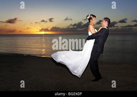 bride and groom twirling round on a beach at sunset - Stock Photo