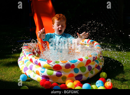 A five year old boy coming down a slide in to a paddling pool in his garden - Stock Photo