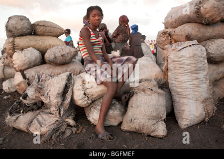A girl sitting on bags of charcoal at the port in Gonaives, Artibonite Department, Haiti - Stock Photo