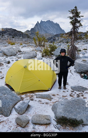 A woman standing a smiling outside her tent in the Enchantment Lakes Wilderness Area, Washington Cascades, USA. - Stock Photo