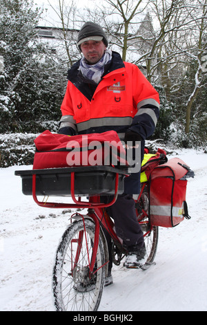 A Royal Mail Postman delivering mail in winter. Woodborough, Nottinghamshire, England, U.K. - Stock Photo