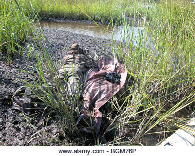 Paparazzi photographer taking a picture lying in muddy swamp Georgia USA - Stock Photo