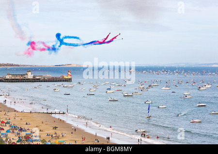 The Red Arrows display team performing their routine over the pier at the Bournemouth Air Festival. Dorset. UK. - Stock Photo