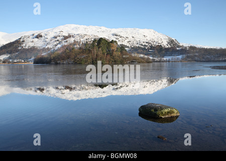 Grasmere with snow clad mountains reflected in the lake, Cumbria, UK - Stock Photo