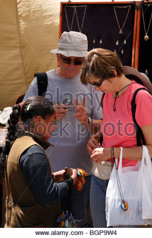 Tourists bargaining to buy ceramic whistle-flutes from an Indian girl in Pisac market, Peru - Stock Photo