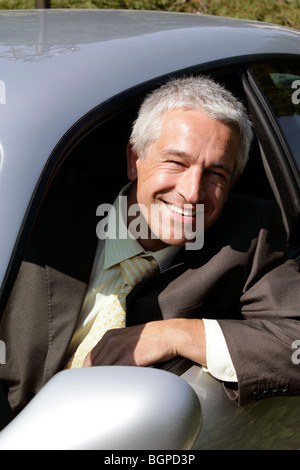 Mature handsome man sitting in car smiling - Stock Photo