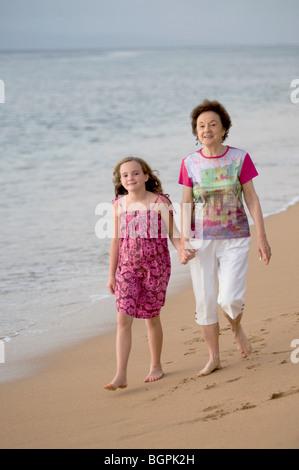 Grandmother and granddaughter at seashore, Maui, Hawaii, USA - Stock Photo