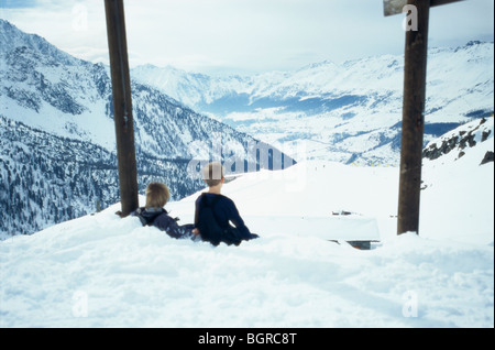 Two boys sitting in the snow up on a mountain, Italy. - Stock Photo