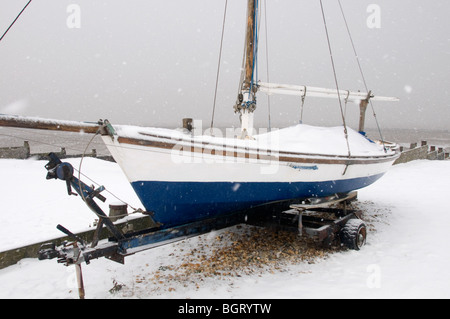 Boat covered in Snow on beach whitstable kent countryside england UK - Stock Photo