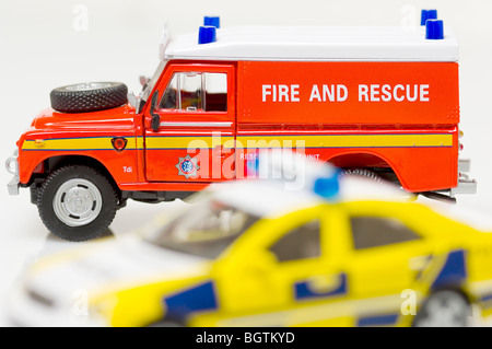 Toy British Fire and Rescue vehicle with Police car in the foreground - Stock Photo