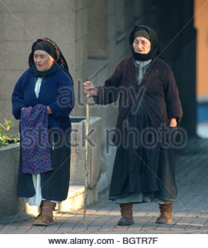 Two old woman walking dressed in black full length Greece - Stock Photo
