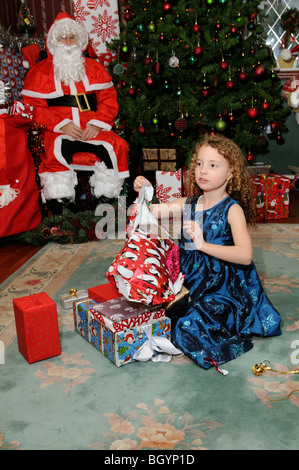Little girl opening Christmas presents from Father Christmas - Stock Photo