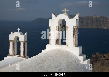Church bell towers overlooking Santorini's caldera and lagoon - Stock Photo