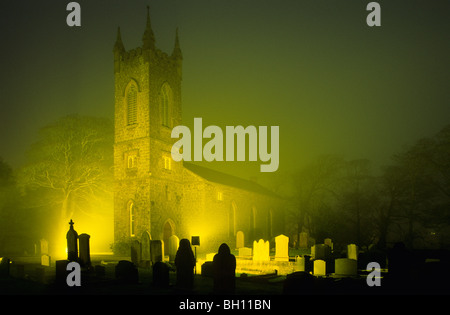 Thurch of St. John the Baptist and a graveyard in a foggy night, Bushmills, County Antrim, Ireland, Europe - Stock Photo