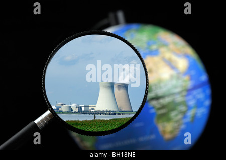 Cooling towers of nuclear power plant seen through magnifying glass held against illuminated terrestrial globe - Stock Photo