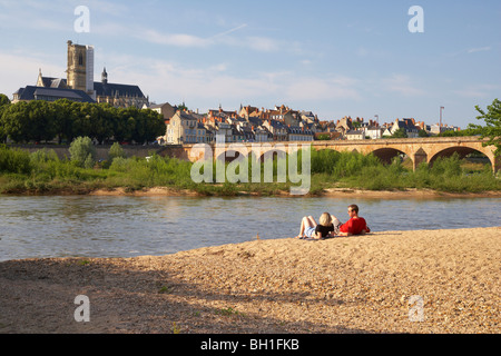 Young couple sitting along the banks of the river Loire, Saint Cyr et Sainte Julitte Cathedral in the background, - Stock Photo