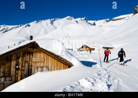 Skiers on slope passing alpine hut, First, Grindelwald, Bernese Oberland, Canton of Bern, Switzerland - Stock Photo