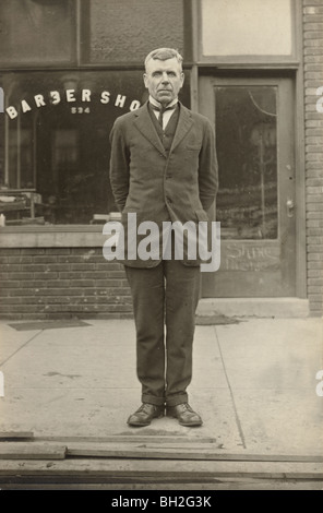 Dour Barber in front of his Barber Shop - Stock Photo