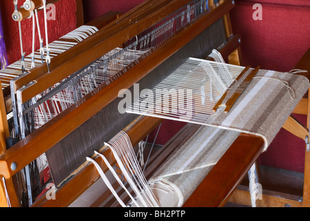 Woollen rug being hand woven on a wooden loom. Kwazulu Natal, South Africa. - Stock Photo