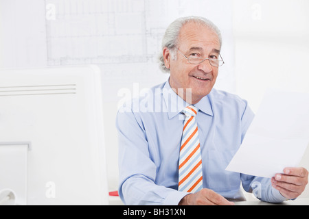 Senior businessman reading a paper - Stock Photo