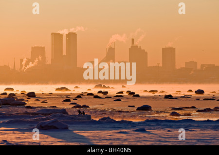 A view to Tallinn city center from the sea, winter, cold weather, sunset, fog, steam - Stock Photo