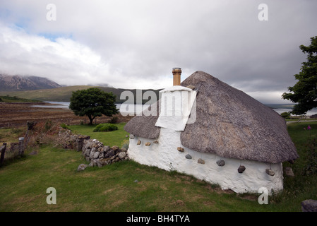 Traditional, historic house with thatched roof and hanging stones, on the Isle of Skye with view on Loch Ainort. - Stock Photo
