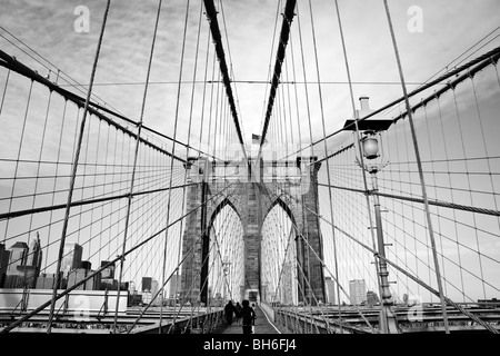 A monochrome view of a tower and suspension cables on the Brooklyn Bridge in New York. The American flag is visible - Stock Photo