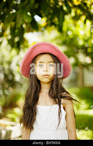 Six year old girl wearing pink hat  outdoors in a garden - Stock Photo