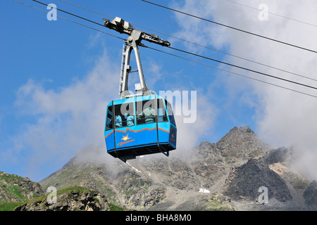 Tourists in cable car / cableway / cable-lift on a cloudy day in the mountains, Swiss Alps, Switzerland - Stock Photo