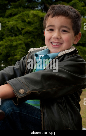 portrait of little Pacific Islander boy on see-saw in park (5 years old) - Stock Photo