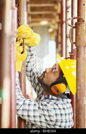 construction worker fixing girder - Stock Photo