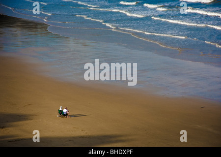 Couple on deserted beach looking out to sea - Stock Photo