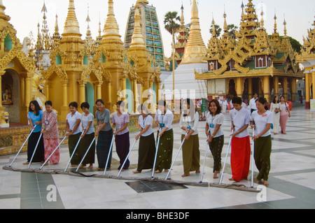 Sweeping ritual by young women on the main terrace, Shwedagon Pagoda, Rangoon, Yangon; Burma, Myanmar - Stock Photo