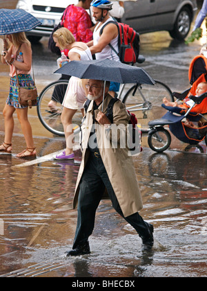 MAN HOLDING UMBRELLA AND WALKING THROUGH PUDDLE IN ROAD  ON SWANSTONE STREET MELBOURNE VICTORIA  AUSTRALIA - Stock Photo