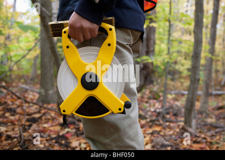 Engineer measuring a construction site with a tape measure - Stock Photo