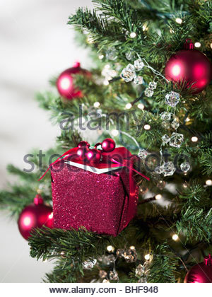 Christmas gift and ornaments on tree - Stock Photo