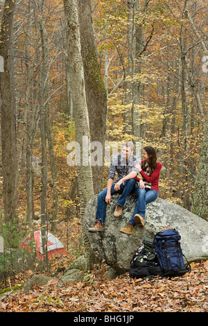 Young couple sitting on boulder in forest - Stock Photo