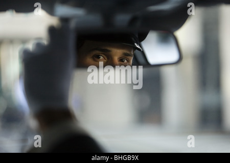 Chauffeur looking in the rear view mirror - Stock Photo