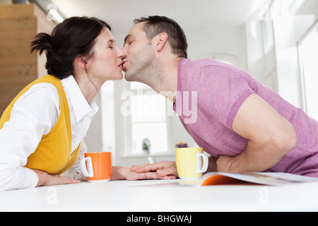 couple leaning over table kissing - Stock Photo